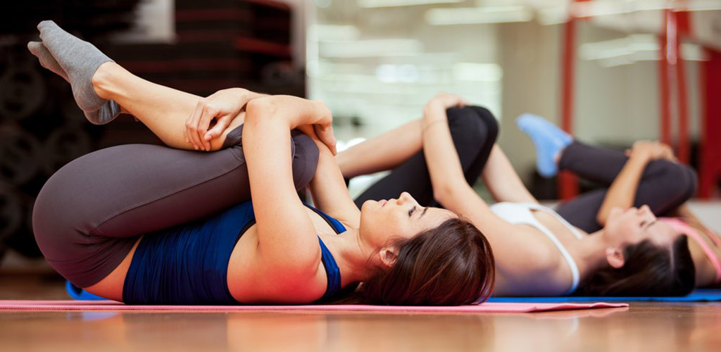 Girls in knees to chest yoga pose at Fitness Station