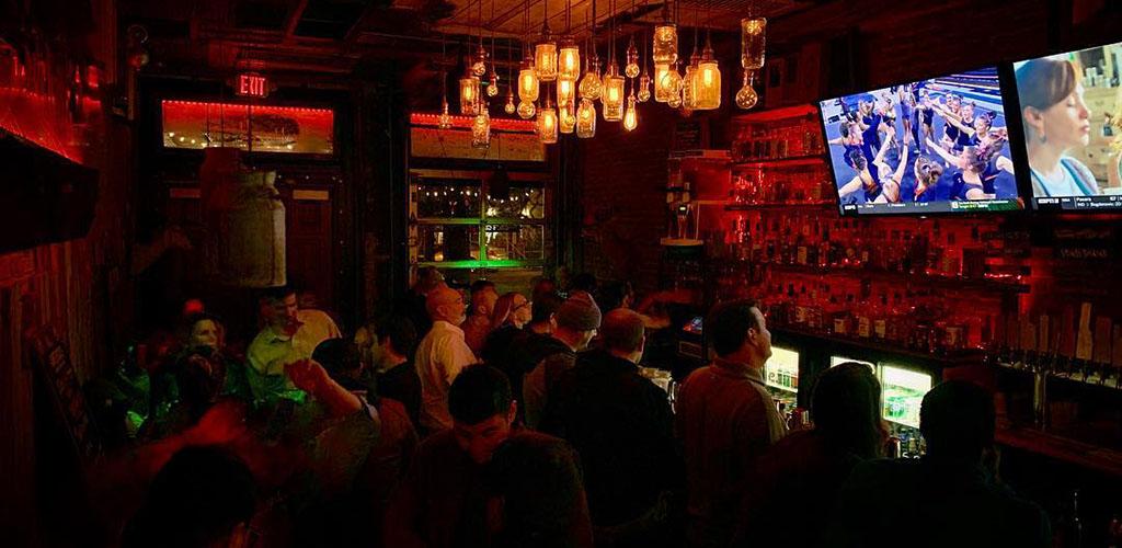 The dim bar illuminated by TVs at Taj