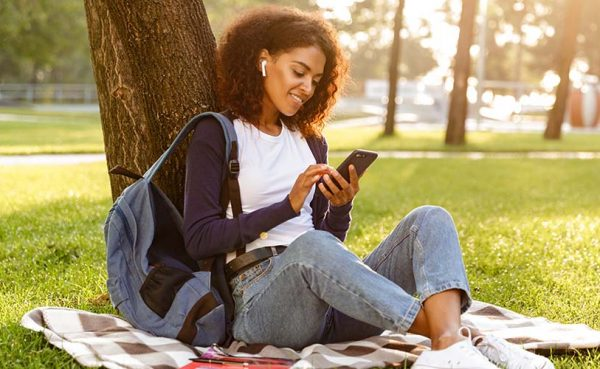 A student listening to music in the park