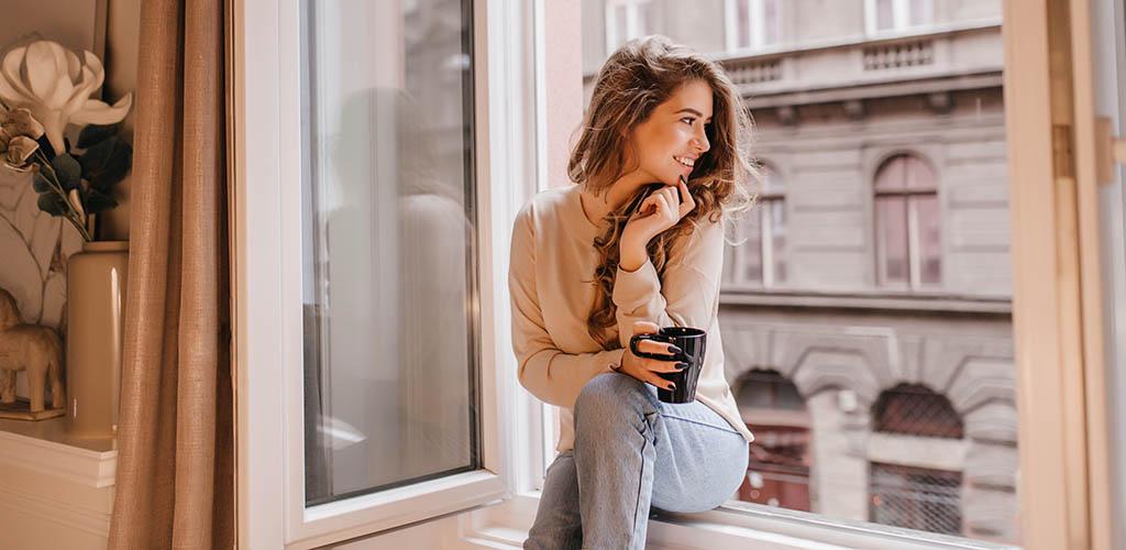Enjoying her coffee by the window