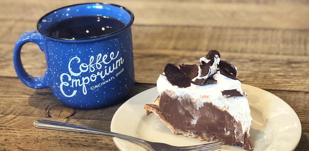 A blue prsopector's mug of coffee with a piece of chocolate pie