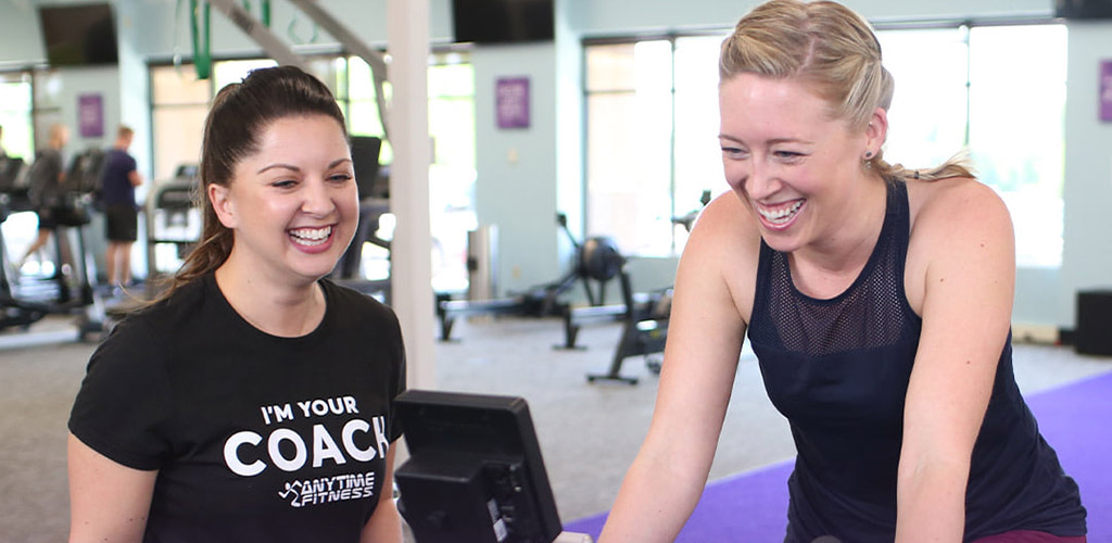 Beautiful blonde training on the stationary bike at Anytime Fitness with her petite brunette coach