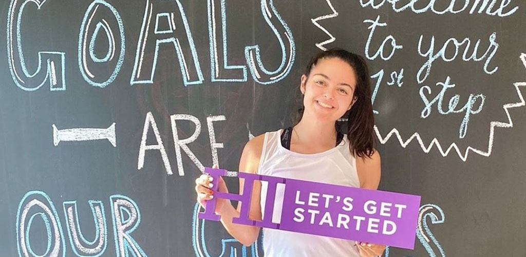 A girl posing in front of a motivational board at Anytime Fitness