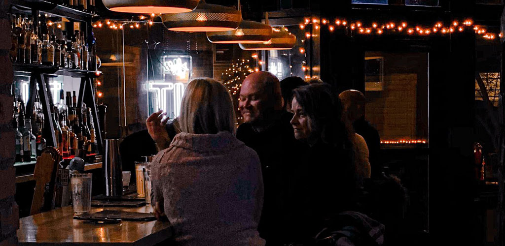 Friends having a drink at Literary Tavern in a dark, intimate setting