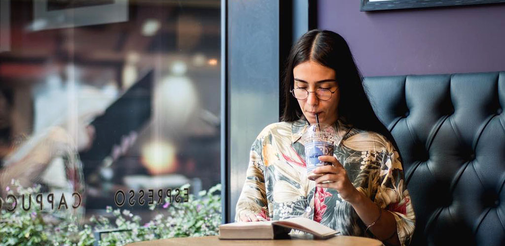 A Manchester girl reading a book and enjoying coffee at Caffe Nero