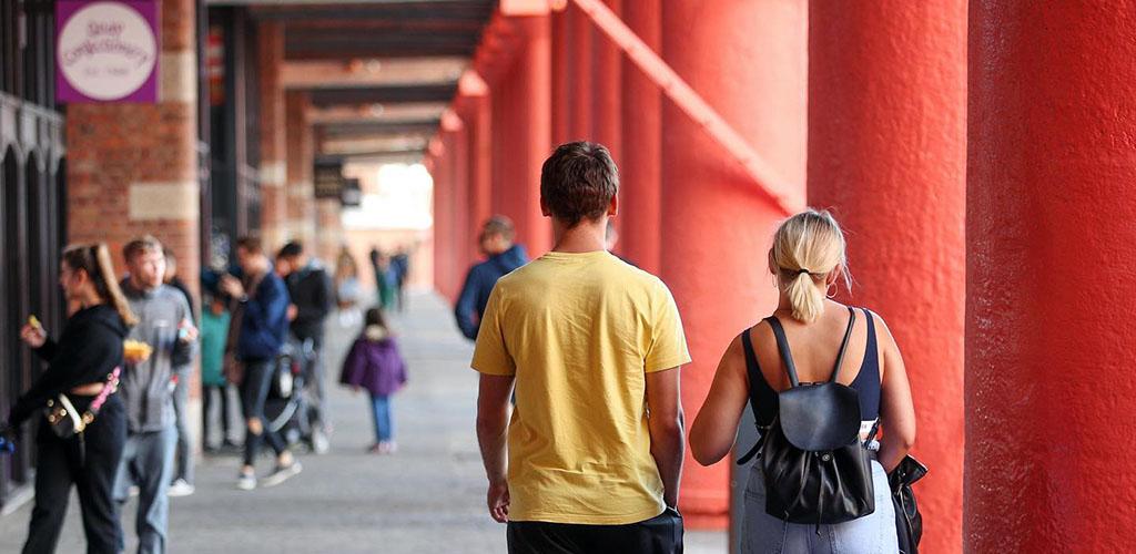 A couple walking along the Royal Albert Dock