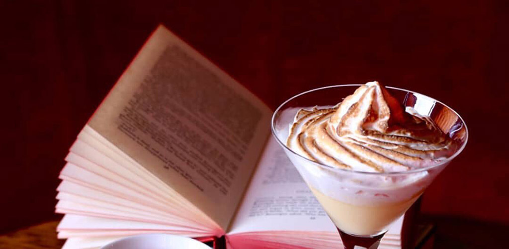 A creamy cocktail and a book from The Library