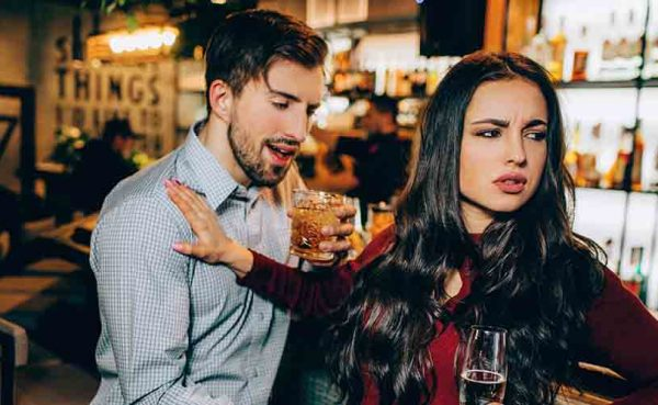 A guy making some big flirting mistakes at a bar